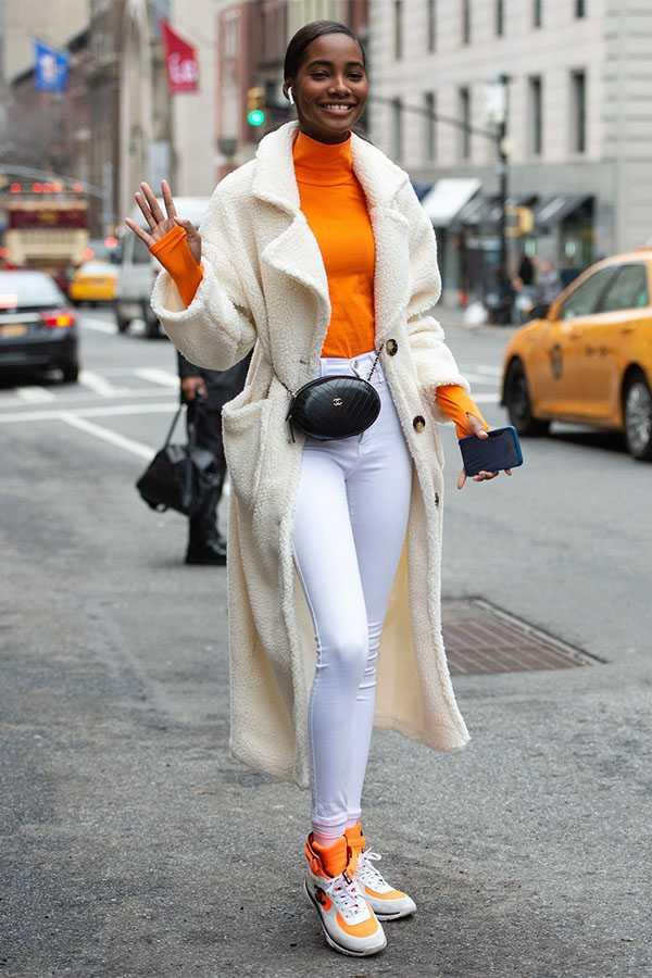Белые джинсы с оранжевой водолазкой